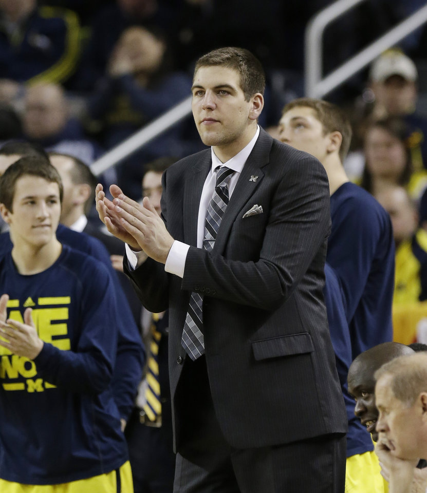 Photo - Michigan forward Mitch McGary cheers the team on from the sidelines during the second half of an NCAA college basketball game against Wisconsin in Ann Arbor, Mich., Sunday, Feb. 16, 2014. (AP Photo/Carlos Osorio)