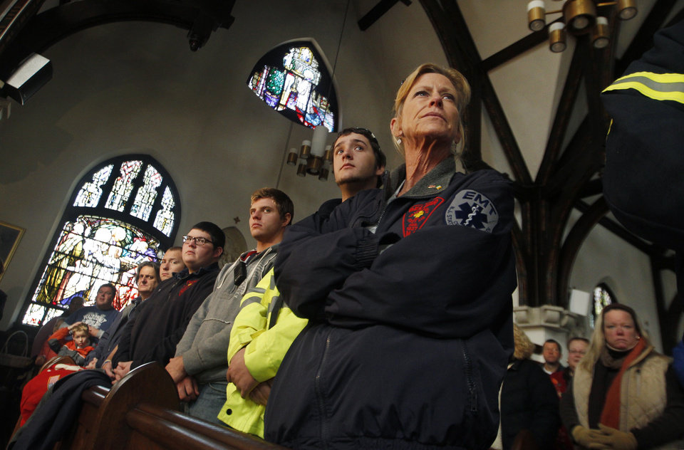 First responders who worked through last Monday's storm surge by Superstorm Sandy, listen as they are acknowledged by Diocese of Trenton American Roman Catholic Bishop David M. O'Connell during services at the Church of Saint Rose in Belmar, N.J., Sunday, Nov. 4, 2012. (AP Photo/Mel Evans)
