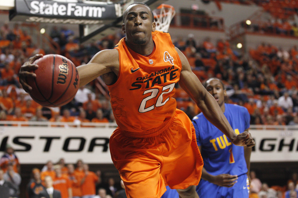Oklahoma State guard Markel Brown (22) reaches for the ball as it goes out of bounds in front of Tulsa forward Rashad Smith (1) in the first half of an NCAA college basketball game in Stillwater, Okla., Wednesday, Nov. 30, 2011. (AP Photo/Sue Ogrocki) ORG XMIT: OKSO104