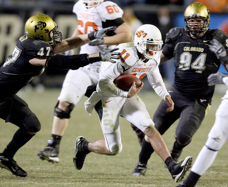 Photo - OSU's Zac Robinson runs between Colorado's Shaun Mohler, left, and Brandon Nicolas during the college football game between Oklahoma State University and the University of Colorado at Folsom Field in Boulder, Colo., Saturday, Nov. 15, 2008. BY BRYAN TERRY, THE OKLAHOMAN