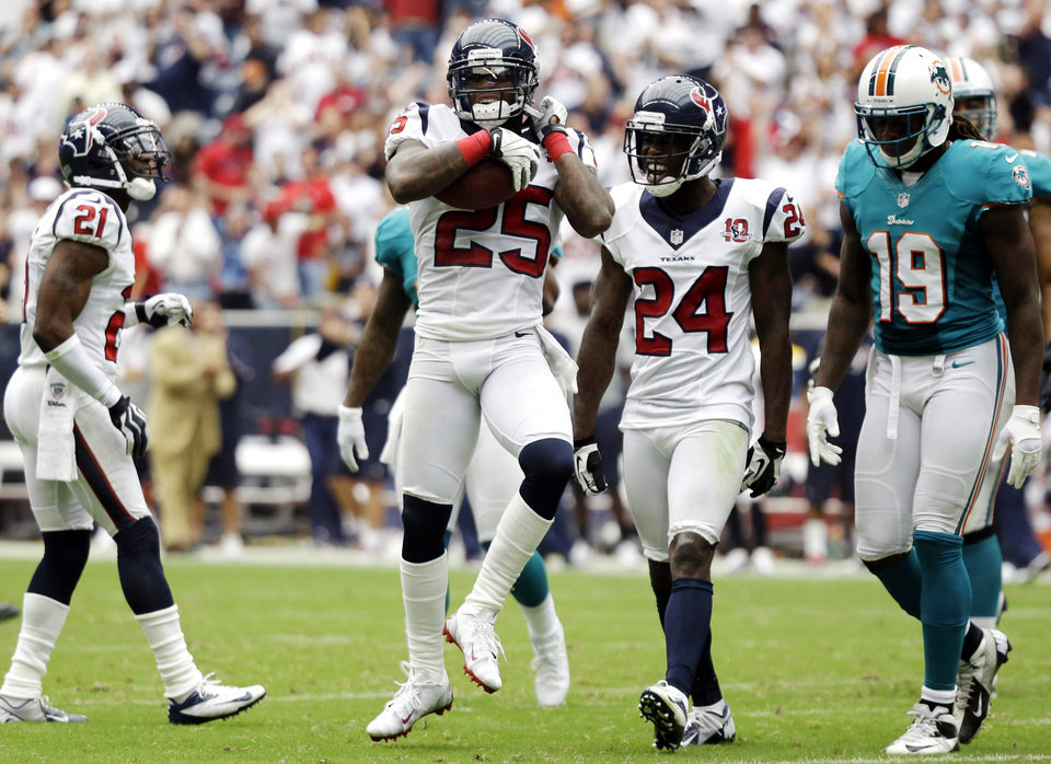 Photo -   Houston Texans cornerback Kareem Jackson (25) celebrates after intercepting a pass against the Miami Dolphins in the second quarter of an NFL football game, Sunday, Sept. 9, 2012, in Houston. (AP Photo/Eric Gay)