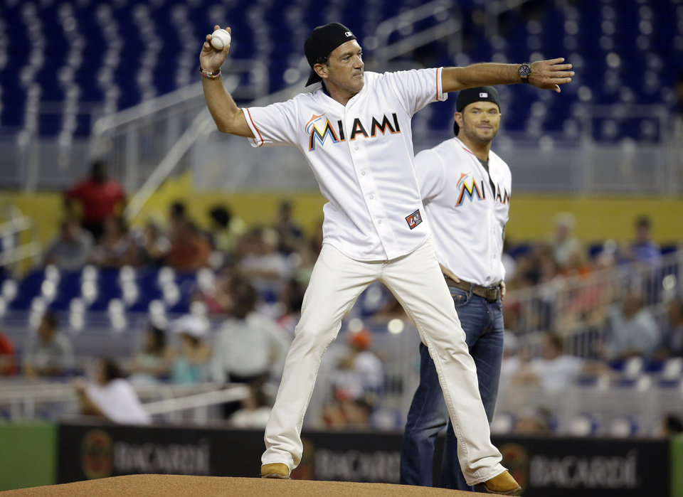 Photo - Actor Antonio Banderas, left, throws out a ceremonial pitch before a baseball game between the Miami Marlins and St. Louis Cardinals, Wednesday, Aug. 13, 2014, in Miami. At right is actor Kellan Lutz. (AP Photo/Lynne Sladky)
