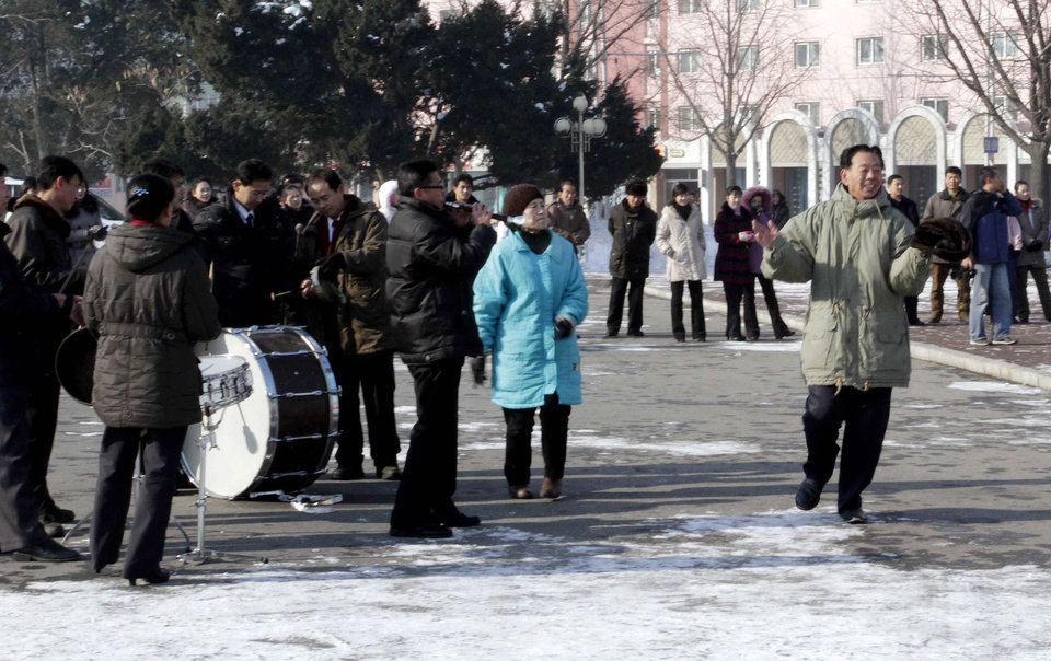 Photo - A North Korean dances to music  in front of the Pyongyang Grand Theatre in Pyongyang, North Korea, to celebrate a rocket launch on Wednesday, Dec. 12, 2012. North Korea appeared to successfully fire a long-range rocket Wednesday, defying international warnings as the regime of Kim Jong Un pushes forward with its quest to develop the technology needed to deliver a nuclear warhead. (AP Photo/Jon Chol Jin) ORG XMIT: PYO108