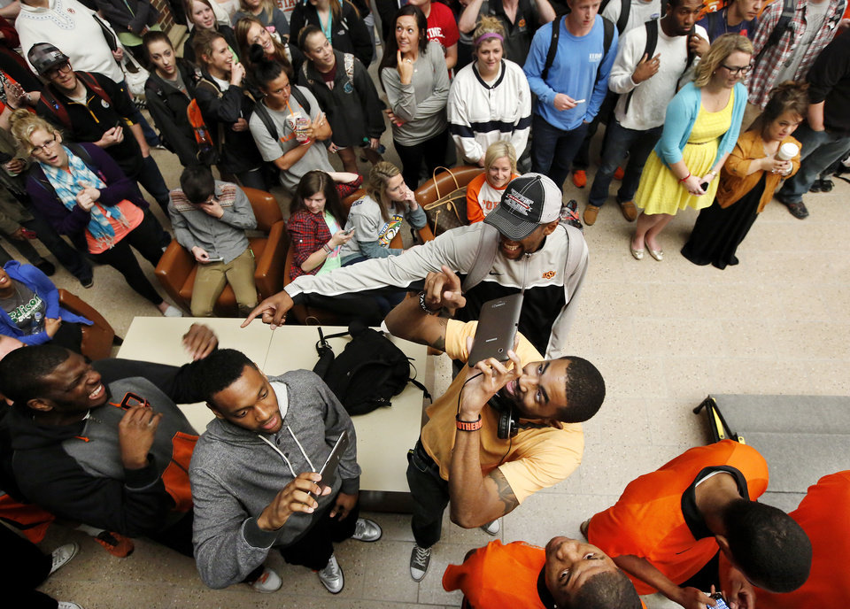 Students crowd near the stage as members of basketball team record the moment with digital recording devices. OSU basketball players Le'Bryan Nash, Markel Brown and Marcus Smart delighted  fans when they announced at a noontime press conference they intend to return for another season as members of the Cowboys basketball team. Cheering fans lined all levels in the Student Union atrium Wednesday, April 17, 2013.    by Jim Beckel, The Oklahoman.