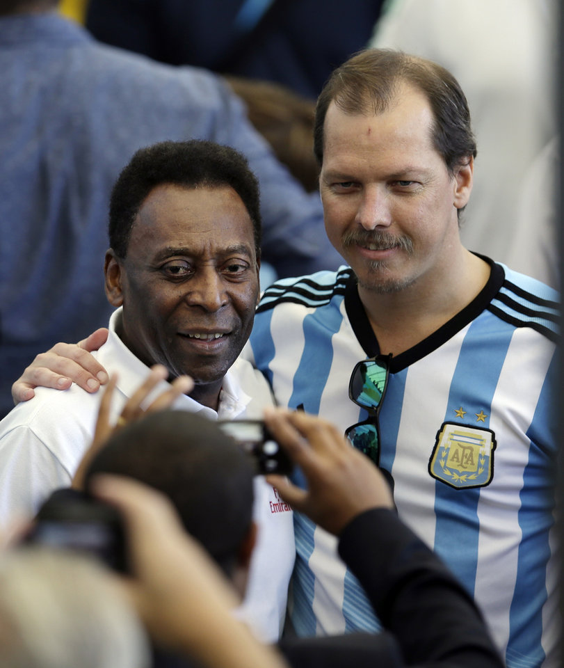 Photo - A man wearing a Argentine jersey has his picture taken with Brazilian soccer legend Pele before the World Cup final soccer match between Germany and Argentina at the Maracana Stadium in Rio de Janeiro, Brazil, Sunday, July 13, 2014. (AP Photo/Hassan Ammar)
