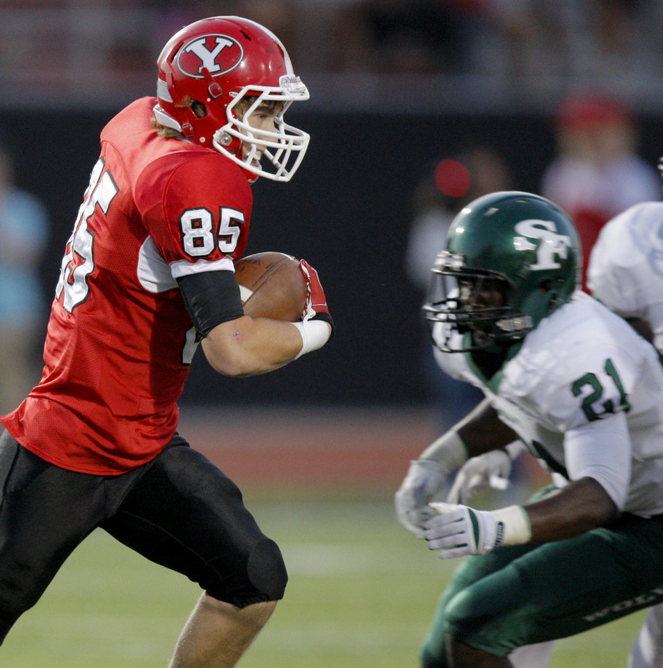 Photo - Yukon's Codey Sanchez, left, runs past Edmond Santa Fe's Ryan Frazier during a 2011 game in Yukon.  Photo by Bryan Terry, The Oklahoman Archives