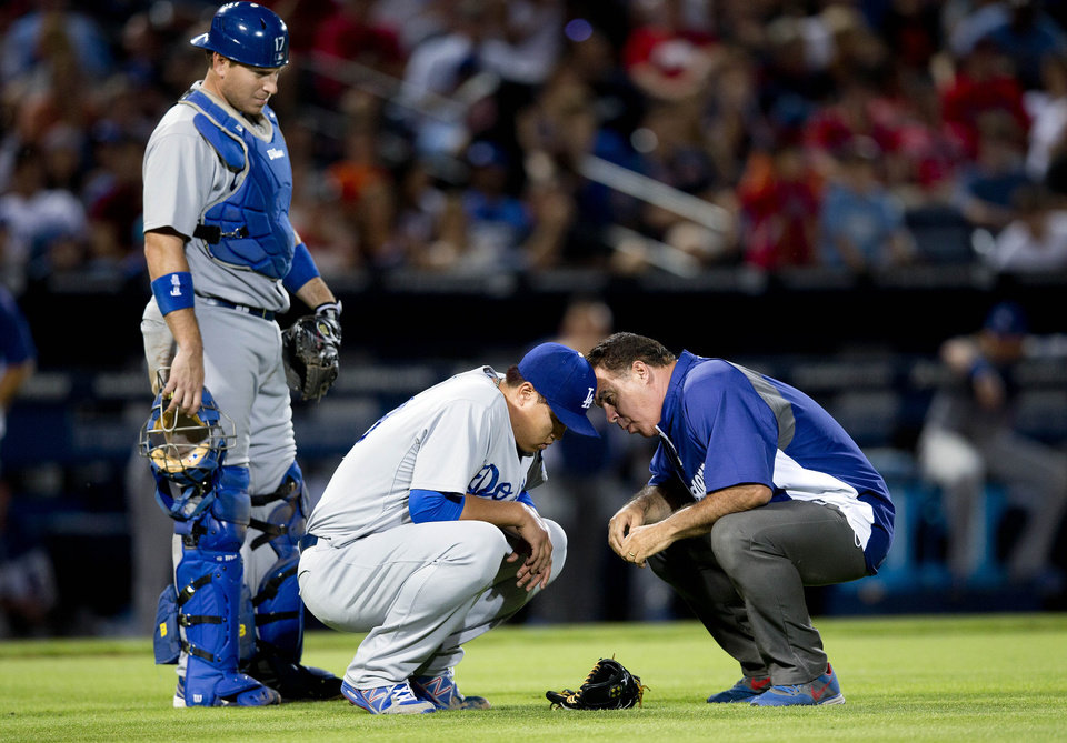 Photo - A member of the Los Angeles Dodgers training staff talks to injured starting pitcher Hyun-Jin Ryu (99) as catcher A.J. Ellis looks on at left, in the sixth inning of a baseball game against the Atlanta Braves Wednesday, Aug. 13, 2014, in Atlanta. Ryu left the game under his own power. (AP Photo/John Bazemore)