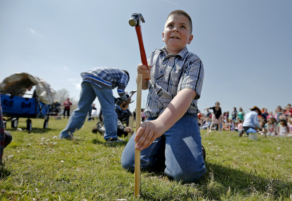 Photo - Kaleb Nelson steaks his claim of land during the Oklahoma Land Run celebration at Mustang Trails Elementary on Monday, April 22, 2013, in Mustang, Okla.   Photo by Chris Landsberger, The Oklahoman