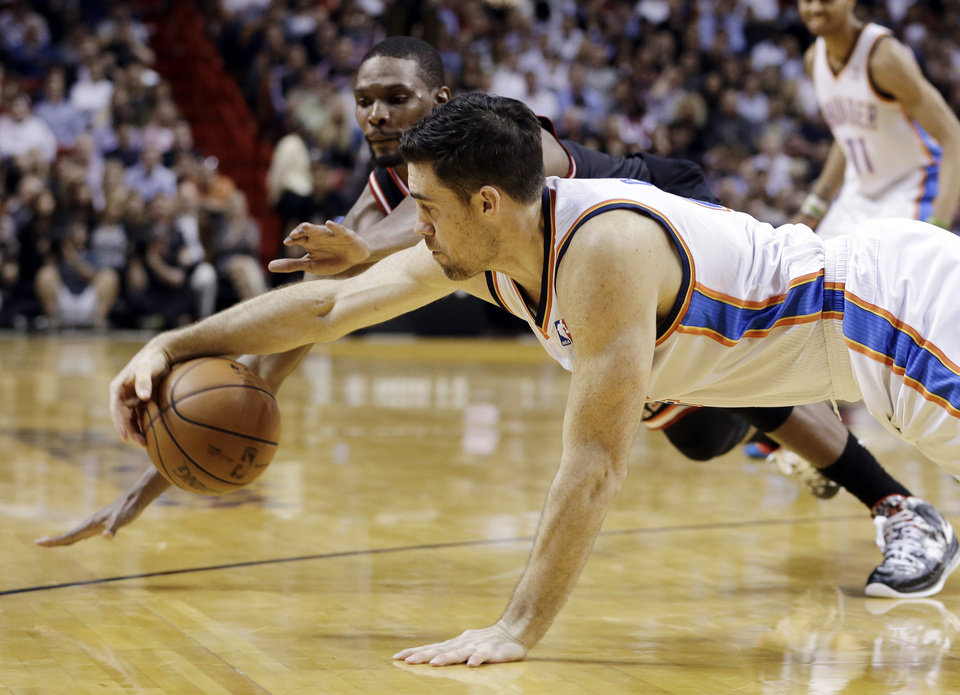 Photo - Oklahoma City Thunder power forward Nick Collison, foreground, recovers a lose ball against Miami Heat center Chris Bosh, background, during the third period of an NBA basketball game in Miami, Wednesday, Jan. 29, 2014. The Thunder won 112-95. (AP PhotoAlan Diaz)