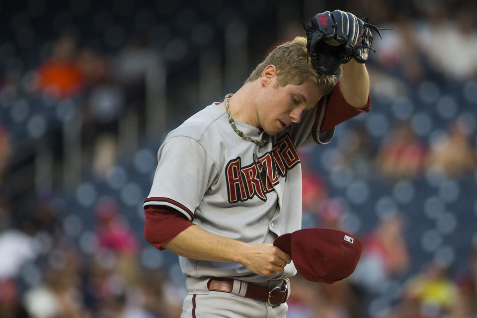Photo - Arizona Diamondbacks starting pitcher Chase Anderson wipes away sweat during the first inning of a baseball game against the Washington Nationals on Tuesday, Aug. 19, 2014, in Washington. (AP Photo/Evan Vucci)