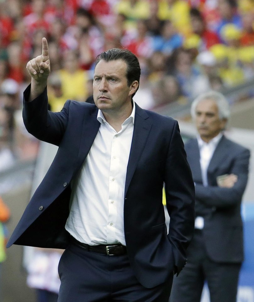 Photo - Belgium's head coach Marc Wilmots gestures as Algeria's head coach Vahid Halilhodzic looks on at rear during the group H World Cup soccer match between Belgium and Algeria at the Mineirao Stadium in Belo Horizonte, Brazil, Tuesday, June 17, 2014. (AP Photo/Hassan Ammar)