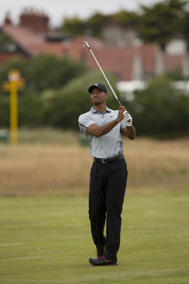 Photo - Tiger Woods of the US walks plays a shot on the 1st fairway during a practice round at the Royal Liverpool Golf Club prior to the start of the British Open Golf Championship, in Hoylake, England, Saturday, July 12, 2014. The 2014 Open Championship starts on Thursday, July 17. (AP Photo/Jon Super)