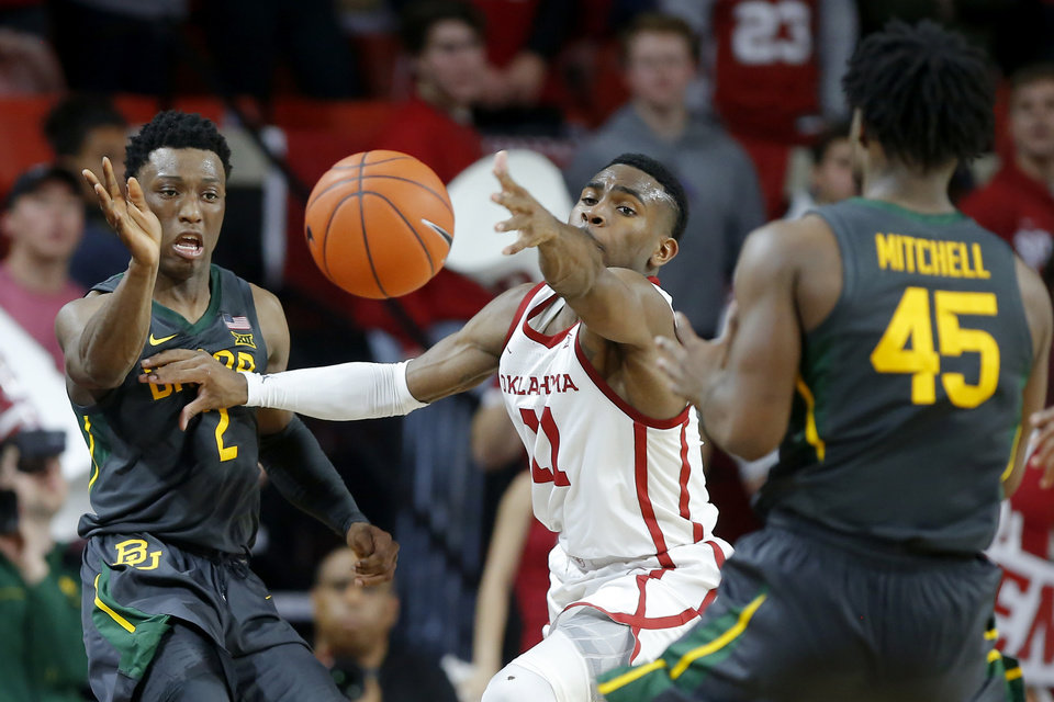 Photo - Baylor's Devonte Bandoo (2) passes the ball past Oklahoma's De'Vion Harmon (11) during a men's NCAA basketball game between the University of Oklahoma Sooners (OU) and the Baylor Bears at the Lloyd Noble Center in Norman, Okla., Tuesday, Feb. 18, 2020. Baylor won 65-54. [Bryan Terry/The Oklahoman]