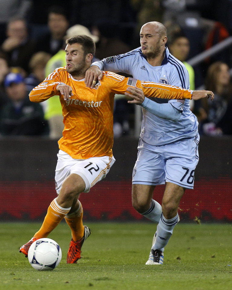 Photo -   Houston Dynamo's Will Bruin (12) and Sporting Kansas City's Aurelien Collin (78) tie up during first half of a MLS soccer playoff game Wednesday, Nov. 7, 2012, in Kansas City, Kan. Sporting KC won the game 1-0 but lost the playoffs 2-1 in aggregate scoring. (AP Photo/Ed Zurga)