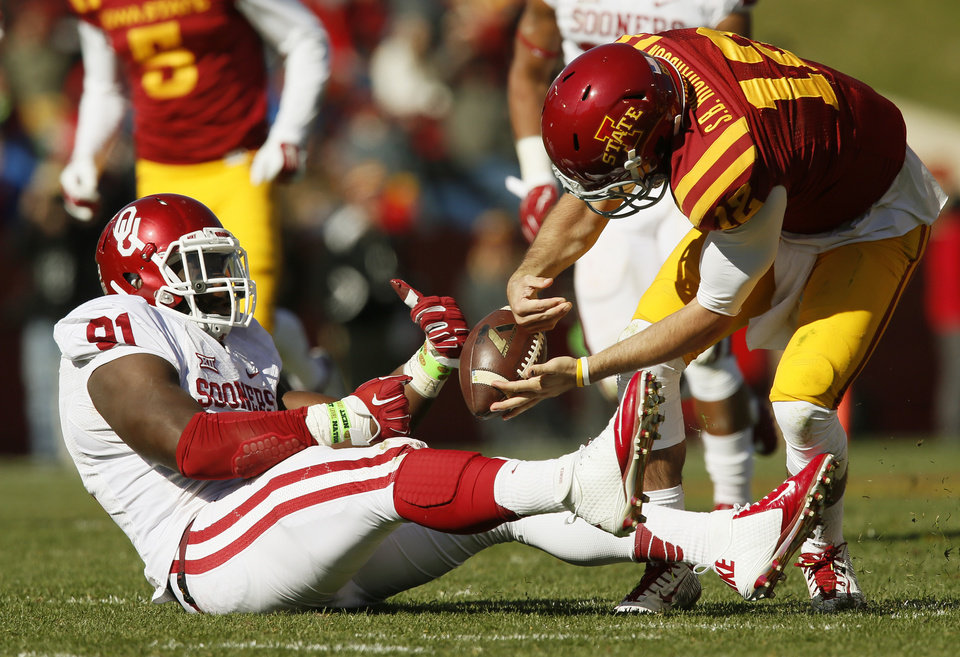 Photo - Iowa State's Sam B. Richardson (12) fumbles the ball after being sacked by Oklahoma's Charles Tapper (91) in the third quarter during a college football game between the University of Oklahoma Sooners (OU) and the Iowa State Cyclones (ISU) at Jack Trice Stadium in Ames, Iowa, Saturday, Nov. 1, 2014. Photo by Nate Billings, The Oklahoman