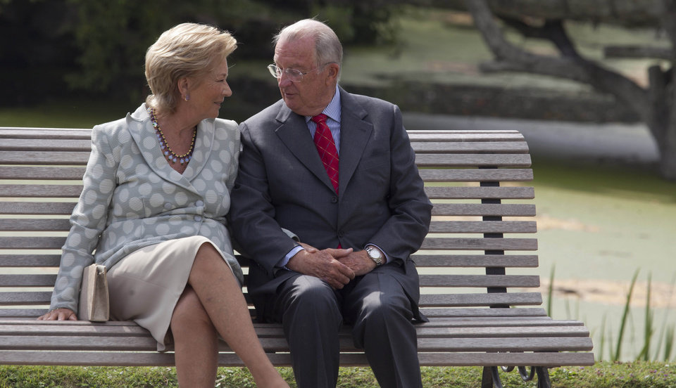 File - In this Sunday, Sept. 2, 2012 file photo, Belgium\'s King Albert II, right, speaks with Queen Paola as they sit on a bench on the grounds of the Royal Palace in Laeken, Belgium. Albert II's kingdom is increasingly threatened by royal-bashing separatists seeking the breakup of Belgium. Now, a book dipping deep into the privacy of kings and princes is adding insult to injury. With its back against the wall, the royal palace sought to strike back in the week of Oct. 29, 2012, seeking action against the journalist who published the book ''Royal Questions'' which is sometimes as rich on dangerous liaisons as it is on the use of anonymous sources. (AP Photo/Virginia Mayo, File)