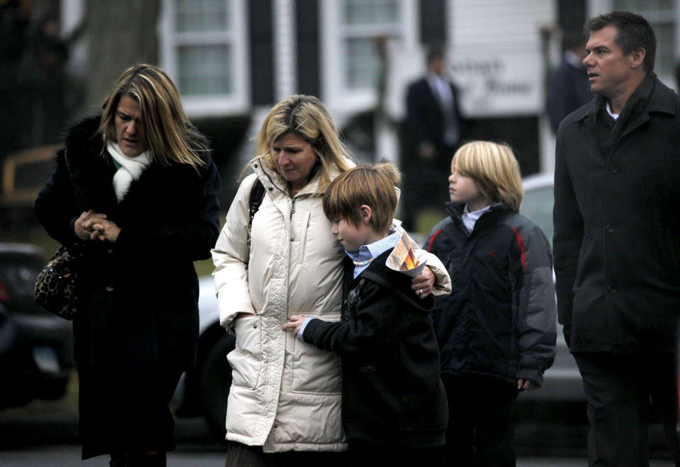 Photo - Mourners leave the funeral service of Sandy Hook Elementary School shooting victim, Jack Pinto, 6, Monday, Dec. 17, 2012, in Newtown, Conn. Pinto was killed when a gunman walked into Sandy Hook Elementary School in Newtown Friday and opened fire, killing 26 people, including 20 children.(AP Photo/David Goldman) ORG XMIT: CTDG122