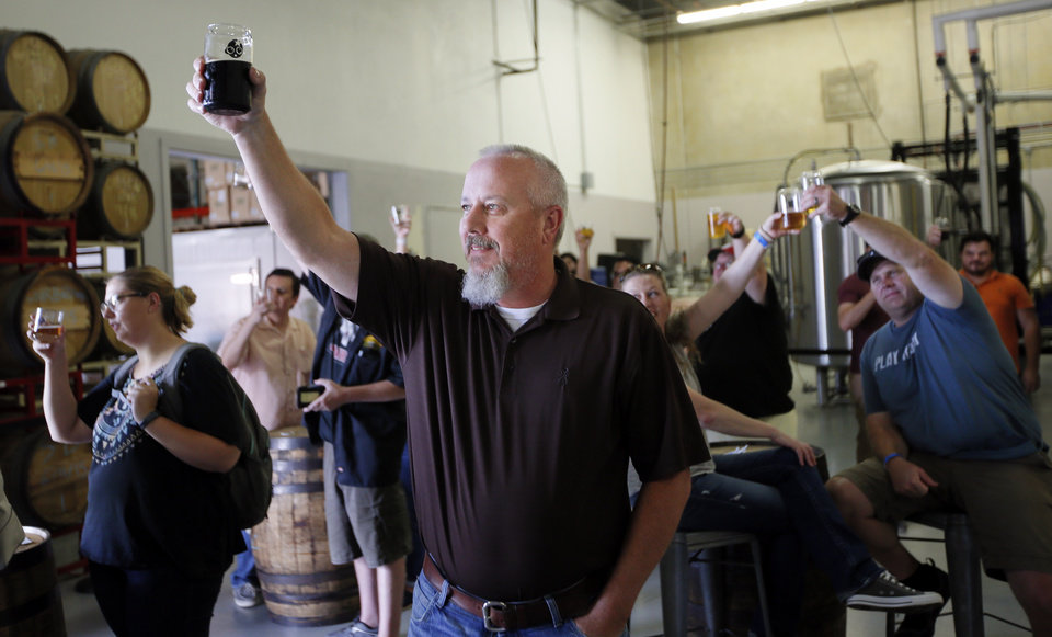 Photo -  Mike Mullins toasts Senate Bill 424 with others at 4:24 p.m. at Anthem Brewing Co. [Photo by Nate Billings, The Oklahoman]