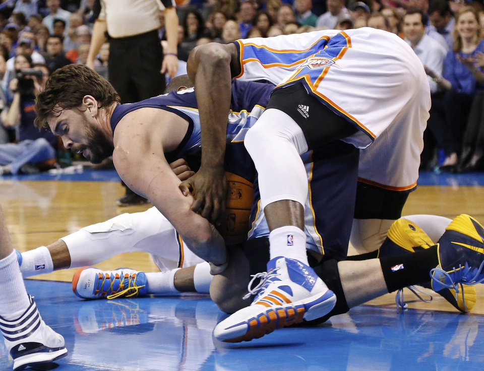 Photo - Memphis Grizzlies center Marc Gasol, left, keeps the ball from Oklahoma City Thunder forward Serge Ibaka, right, during the first quarter of an NBA basketball game in Oklahoma City, Friday, Feb. 28, 2014. (AP Photo/Sue Ogrocki)