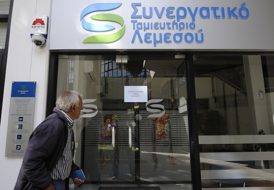 An elderly man holds his bank passbook as he looks through the windows of a closed cooperative bank shop in Limassol, Cyprus, Saturday, March 16, 2013. Many rushed to cooperative banks which are open Saturdays in Cyprus, after learning that the terms of a bailout deal that the cash-strapped country hammered out with international lenders, includes a one-time levy on bank deposits. The move, decided in an extraordinary meeting of the finance ministers of the 17-nation eurozone in the early hours Saturday, is a major departure from established policies.  (AP Photo/Pavlos Vrionides)