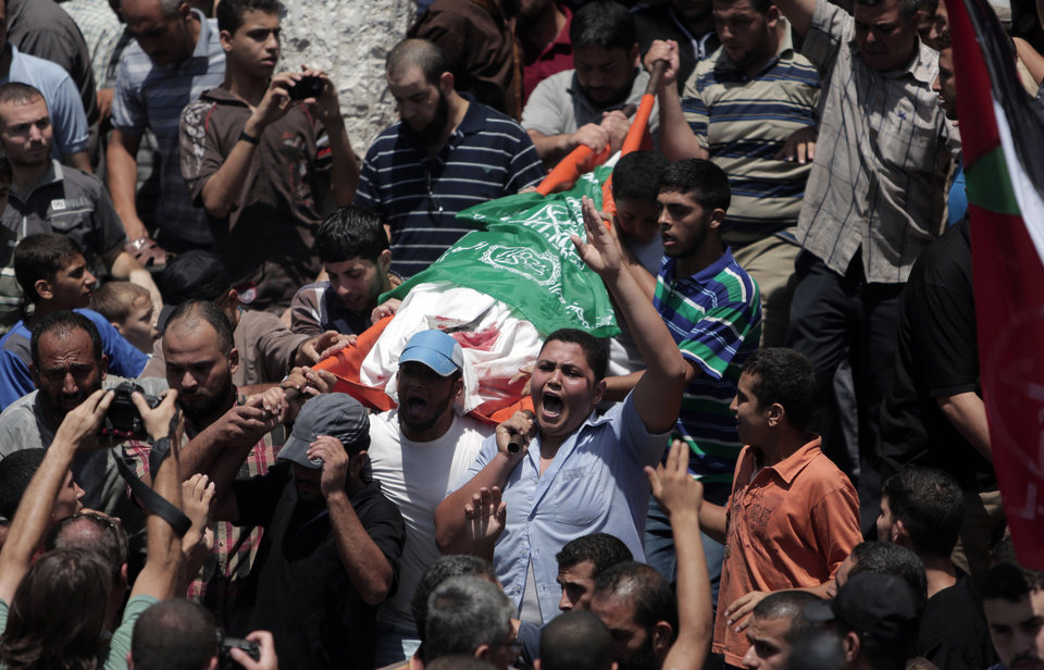 Photo - Mourners chant angry slogans during the funeral of Palestinian Widad Mustafa Deif, 27, who was killed along with her 8-month-old son Ali Mohammed Deif in Israeli strikes in Gaza City late Tuesday, during their funeral in Jabaliya refugee camp in the northern Gaza Strip, Wednesday, Aug. 20, 2014. Widad was the wife of Mohammed Deif, the leader of the Hamas military wing. (AP Photo/Khalil Hamra)