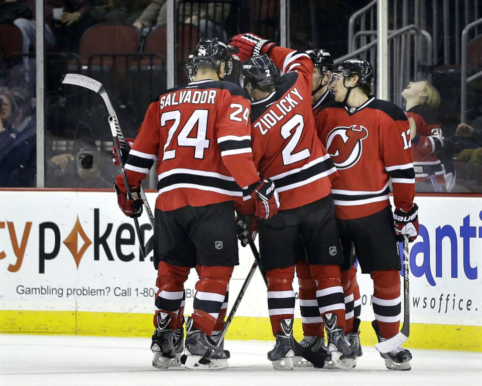 Photo - New Jersey Devils players swarm on Damien Brunner, of the Czech Republic, after he scored a goal during the first period of an NHL hockey game against the Toronto Maple Leafs, Sunday, March 23, 2014, in Newark, N.J. (AP Photo/Mel Evans)