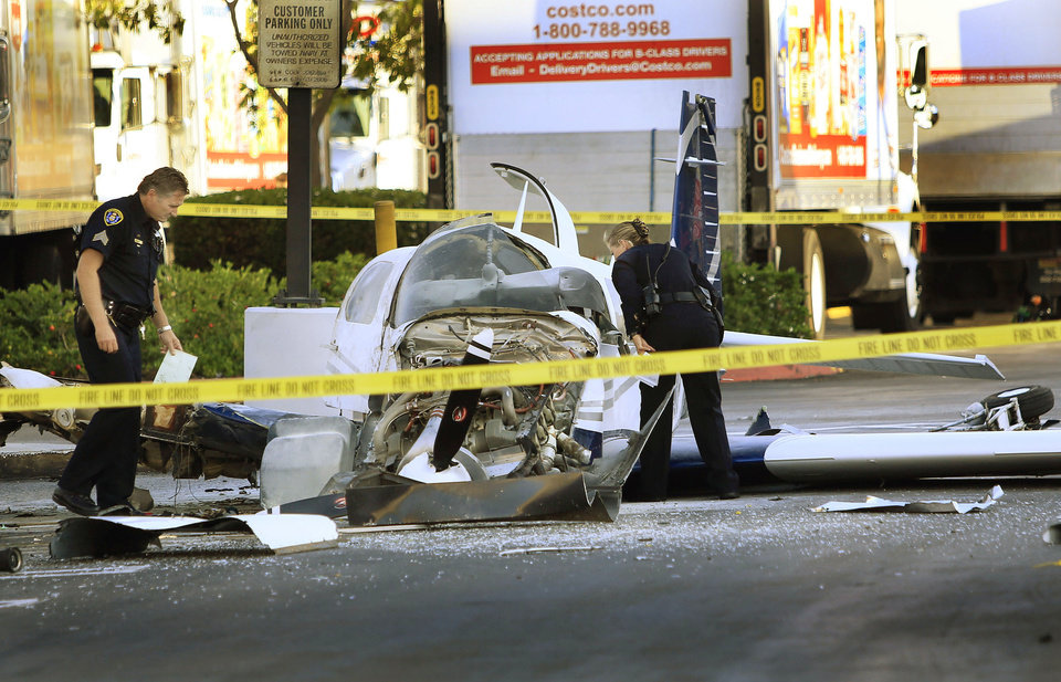 Photo - San Diego police examine the wreckage of a small plane in the parking lot of shopping center Wednesday, July 30, 2014, in San Diego. Police said that one woman was killed and one hurt in the crash. (AP Photo/U-T San Diego, David Brooks) NO SALES; MANDATORY CREDIT; TV OUT; MAGAZINES OUT; COMMERCIAL INTERNET OUT