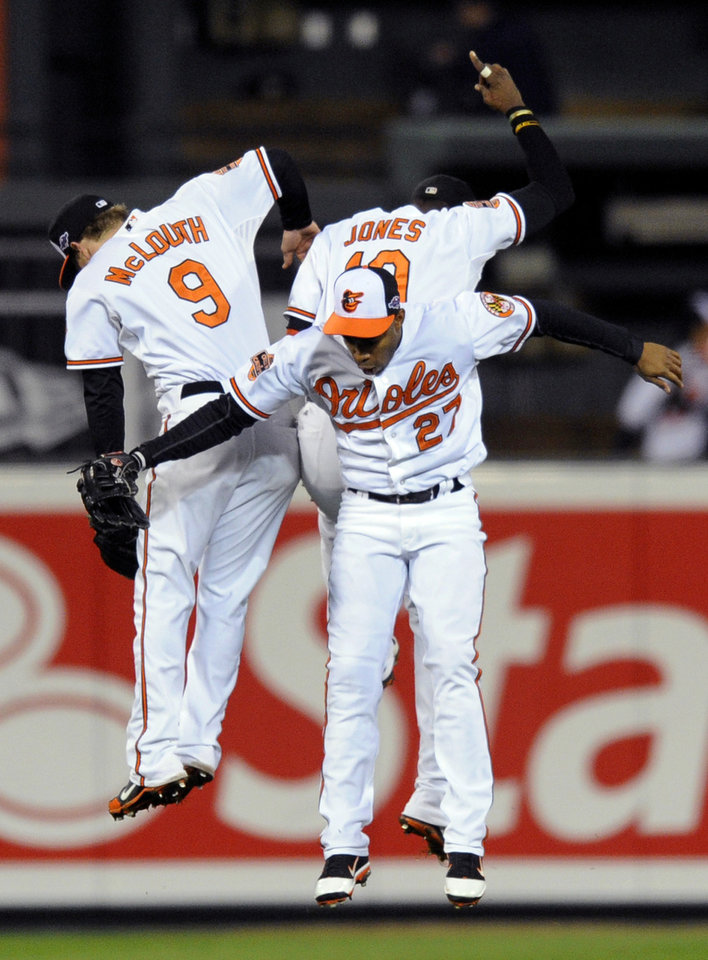 Baltimore Orioles' Nate McLouth, left, Endy Chavez (27) and Adam Jones celebrate winning Game 2 of the American League division baseball series against the New York Yankees on Monday, Oct. 8, 2012, in Baltimore. Baltimore won 3-2. (AP Photo/Nick Wass)