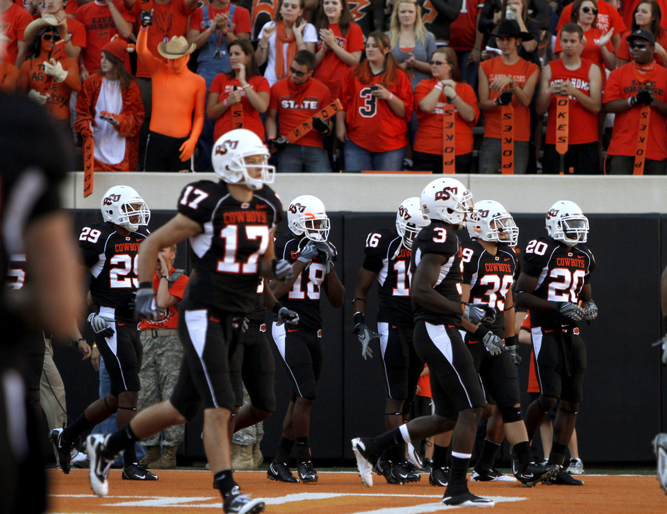 Photo - The OSU team takes the field to warm up before the college football game between Texas A&M University and Oklahoma State University (OSU) at Boone Pickens Stadium in Stillwater, Okla., Thursday, Sept. 30, 2010. Photo by Bryan Terry, The Oklahoman