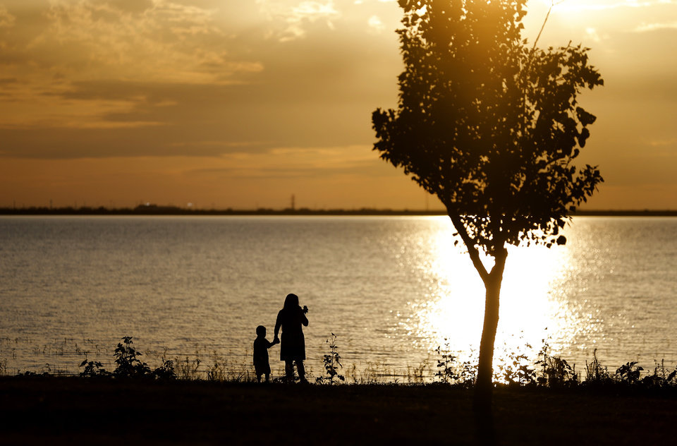 Photo - People walk along the shore of Lake Hefner at sunset in Oklahoma City, Tuesday, July 1, 2014. Photo by Bryan Terry, The Oklahoman