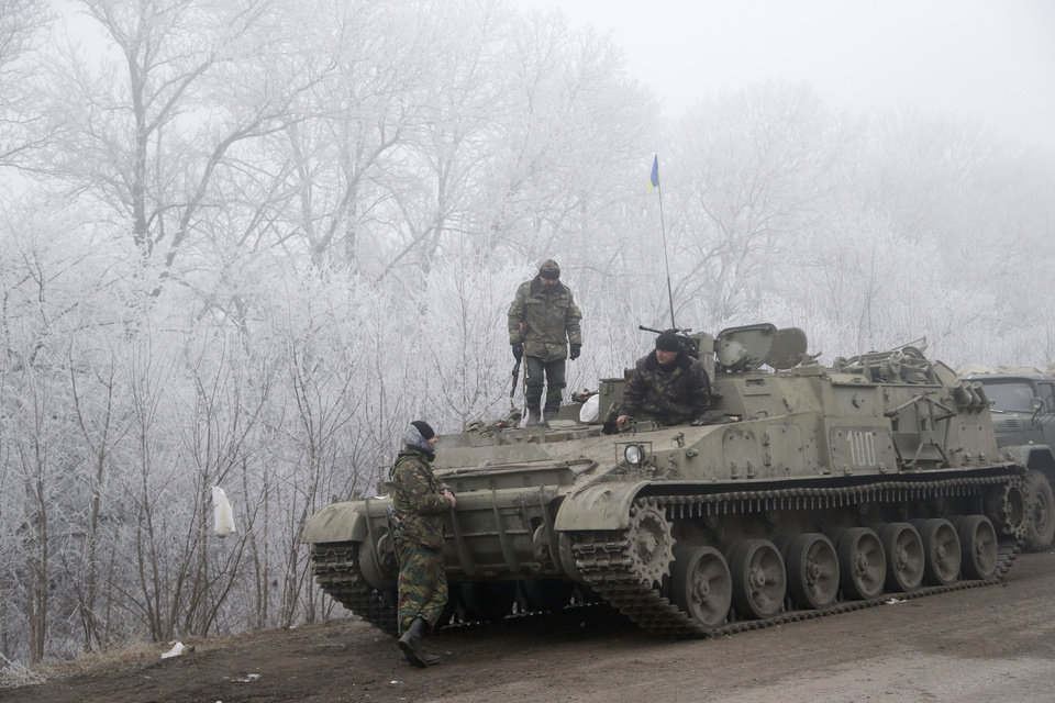 Photo - Ukrainian government soldiers rest by armored vehicle on the road between the towns of Dabeltseve and Artemivsk, Ukraine, Sunday, Feb. 15, 2015. International attention will be focused in the coming days on the strategic railway hub of Debaltseve, where Ukrainian government forces have for weeks been fending off severe onslaughts from pro-Russian separatists. A cease-fire was declared in eastern Ukraine, kindling slender hopes of a reprieve from a conflict that has claimed more than 5,300 lives. (AP Photo/Petr David Josek)