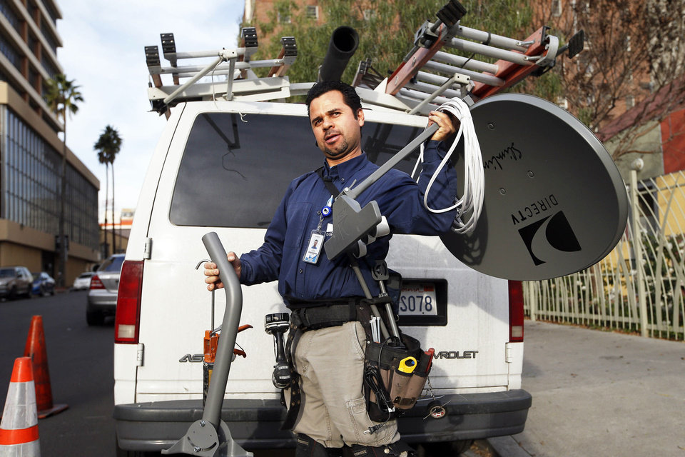 Cesar Ramirez, a subcontractor for DirecTV, gets ready to install a DirecTV satellite dish in Los Angeles.  AP Photo