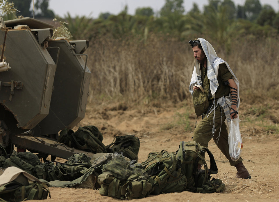 Photo - An Israeli soldier walks with a prayer shawl near the border of Israel and Gaza, Friday, July 18, 2014. Israeli troops pushed deeper into Gaza on Friday to destroy rocket launching sites and tunnels, firing volleys of tank shells and clashing with Palestinian fighters in a high-stakes ground offensive meant to weaken the enclave's Hamas rulers. Israel launched the operation late Thursday, following a 10-day campaign of more than 2,000 air strikes against Gaza that had failed to halt relentless Hamas rocket fire on Israeli cities. (AP Photo/Tsafrir Abayov)