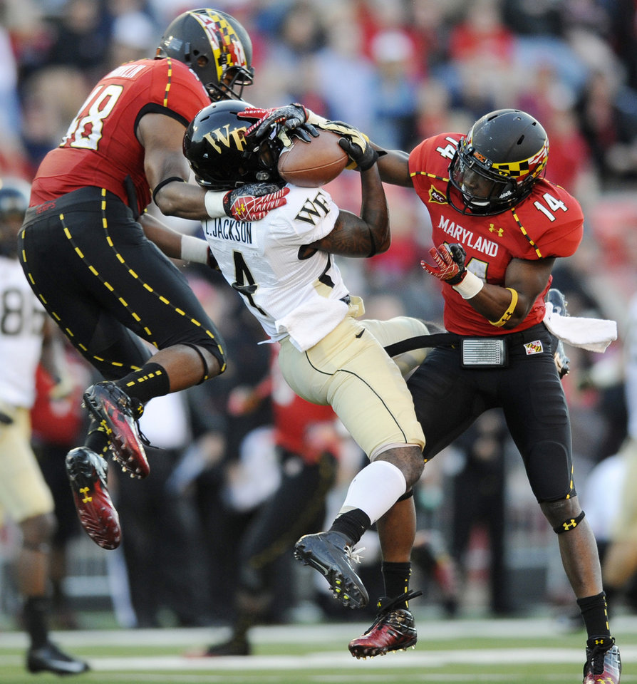 Photo -   Maryland defensive backs Eric Franklin (48) and Jeremiah Johnson (14) break up a pass intended for Wake Forest wide receiver Lovell Jackson, center, during the second half of an NCAA football game, Saturday, Oct. 6, 2012, in College Park, Md. Maryland won 19-14. (AP Photo/Nick Wass)