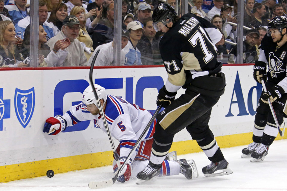Photo - Pittsburgh Penguins' Evgeni Malkin (71) collides with New York Rangers' Dan Girardi (5) in the second period of game 2 of a second-round NHL playoff hockey series in Pittsburgh Sunday, May 4, 2014. (AP Photo/Gene J. Puskar)