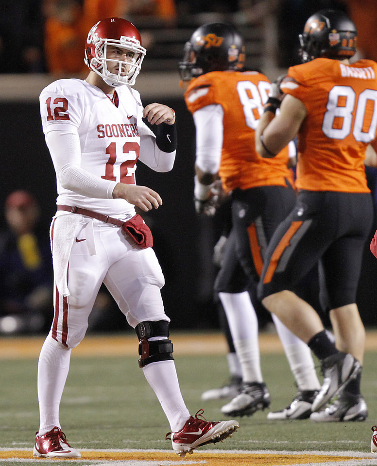 Photo - Oklahoma's Landry Jones (12) walks off the field after being stopped on a drive during the Bedlam college football game between the Oklahoma State University Cowboys (OSU) and the University of Oklahoma Sooners (OU) at Boone Pickens Stadium in Stillwater, Okla., Saturday, Dec. 3, 2011. Photo by Chris Landsberger, The Oklahoman