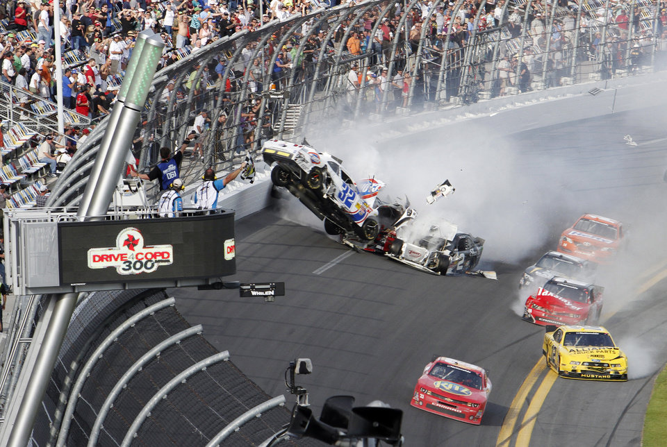 Kyle Larson's car (32) gets airborne during a multi-car wreck on the final lap of the NASCAR Nationwide Series auto race Saturday, Feb. 23, 2013, at Daytona International Speedway in Daytona Beach, Fla. Tony Stewart, in the red car at front, won the race. (AP Photo/David Graham)