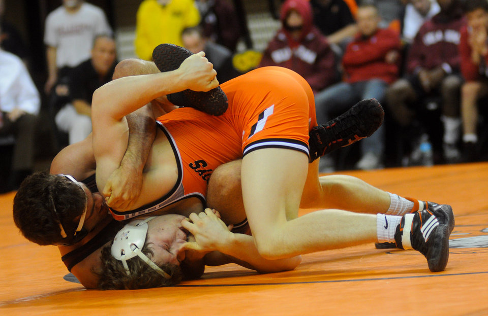 Photo - At 157 pounds, Oklahoma State wrestler Alex Dieringer takes down Oklahoma's Justin DeAngelis. Dieringer won the bout by a major decision score of 13-4 in Oklahoma State's 40-3 victory over Oklahoma at Gallagher Iba Arena in Stillwater, Okla. during the Big 12 Dual Finals on March 8, 2013. KT King/For the Oklahoman