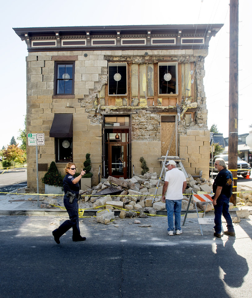 Photo - A Napa police sergeant asks spectators to move further from the damaged Vintner's Collective tasting room in Napa, Calif., following an earthquake Sunday, Aug. 24, 2014. Officials in the city of Napa say 15 to 16 buildings are no longer inhabitable after Sunday's magnitude-6.0 earthquake, and there is only limited access to numerous other structures. (AP Photo/Noah Berger)