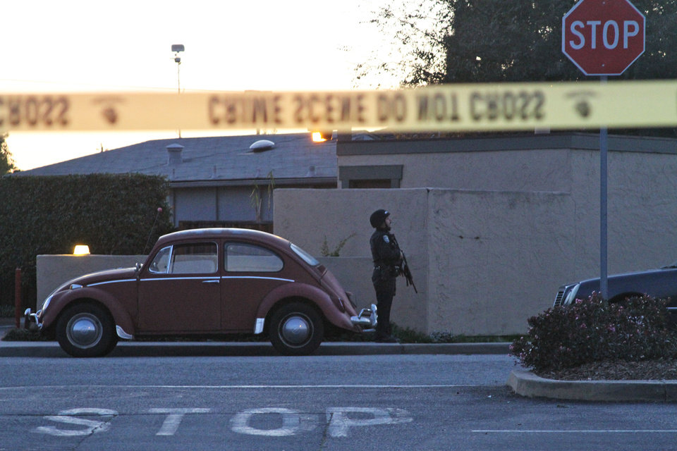 Photo - A police officer secures the shooting scene near N. Branciforte Avenue and Doyle Street Tuesday, Feb. 26, 2013 in Santa Cruz, Calif., where two Santa Cruz Police Detectives were shot and killed. The officers were killed while investigating a sexual assault, and a suspect was also fatally shot, authorities said. (AP Photo/Thomas Mendoza)