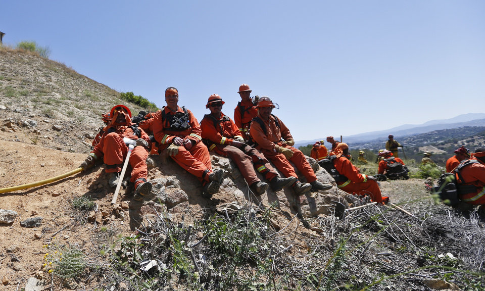 Photo - Firefighters take a break on a hillside after hours of work Thursday, May 15, 2014, in San Marcos, Calif. Gusty winds failed to return Thursday morning in San Diego County wildfire areas and authorities said it was a window of opportunity to make further gains against flames that burned homes and drove tens of thousands from their homes. (AP Photo)