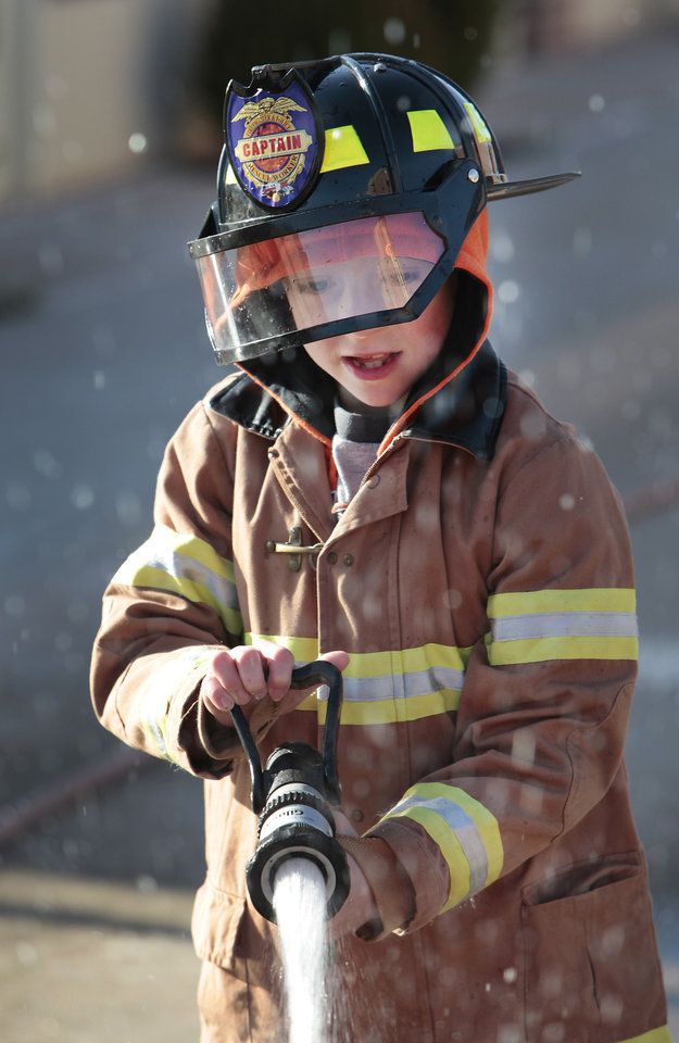 Zachery Duck, 7, sprays a fire hose during Edmond Fire Department's Children's Safety Challenge over spring break. PHOTO BY DAVID MCDANIEL, THE OKLAHOMAN. <strong>David McDaniel - The Oklahoman</strong>
