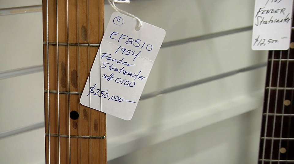 Photo - A store tag in George Gruhn's music shop is seen showing the price for the first production model Fender Stratocaster guitar, Tuesday, March 18, 2014, in Nashville, Tenn. The sunburst-finish Strat bears the serial number 0100. Although some Strats have lower numbers that begin with 0001, Gruhn says they actually were manufactured later in that first year of production. (AP Photo/Kristin M. Hall)