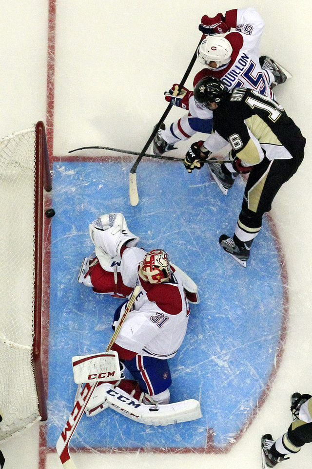 Pittsburgh Penguins center Brandon Sutter, second from left, beats Montreal Canadiens goalie Carey Price (31) with Montreal Canadiens defenseman Francis Bouillon (55) defending during the second period of an NHL hockey game in Pittsburgh Wednesday, April 17, 2013. The Penguins won 6-4. (AP Photo/Gene Puskar)