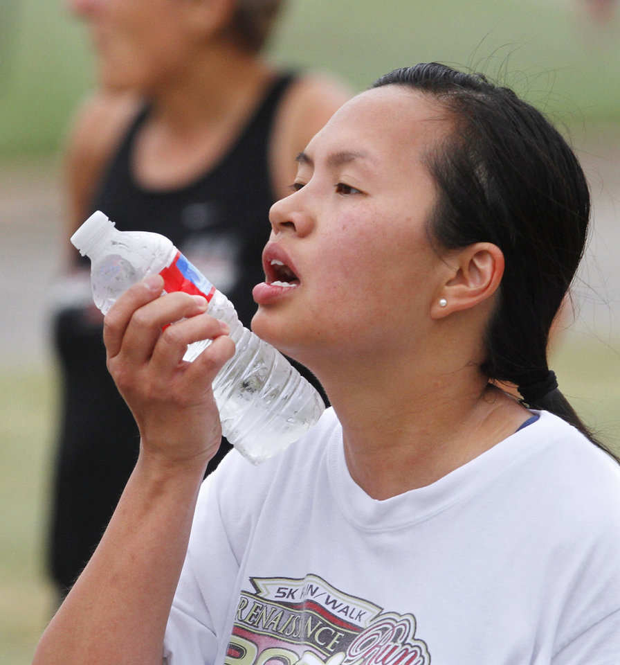 A runner rolls a cold bottle of water across her face after finishing the race. The Renaissance Run, a  5K run and walk begins at 8:30 a.m. at the Midwest City Community Center. Following the race, runners are invited to enjoy a pancake breakfast  at Midwest Regional Medical Center, 2825 Parklawn Drive on Saturday, Sep. 15, 2012,  Photo by Jim Beckel, The Oklahoman.