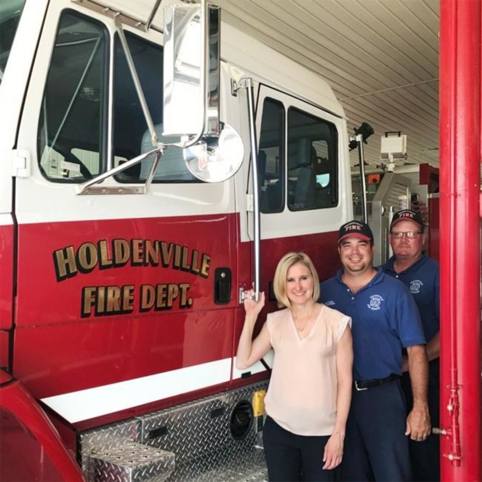 Photo -  Corterra Energy CEO Valerie Mitchell is shown with Holdenville firefighters after making a corporate donation toward the town's annual July Fourth fireworks celebration that the fire department spearheads. [PROVIDED]