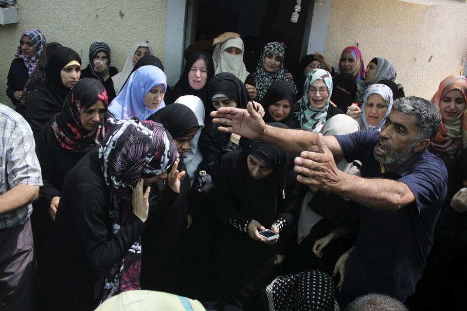 Photo - Palestinian relatives cry during the funeral for a senior commander of the Hamas military wing, Mohammed Abu Shamaleh, who was killed in early morning Israeli strikes, at his family house in the Rafah refugee camp in the southern Gaza Strip, Thursday, Aug. 21, 2014. The pre-dawn strike leveled a four-story house in a densely populated neighborhood of Rafah, killing at least six people, including Abu Shamaleh and two other senior Hamas commanders. (AP Photo/Hatem Ali)