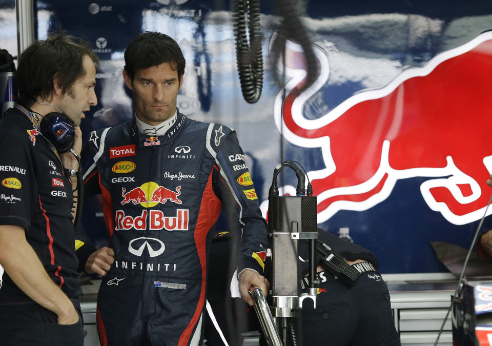 Photo -   Red Bull driver Mark Webber, right, of Australia talks with a team mechanic during the first practice session for the Korean Formula One Grand Prix at the Korean International Circuit in Yeongam, South Korea, Friday, Oct. 12, 2012. (AP Photo/Mark Baker)