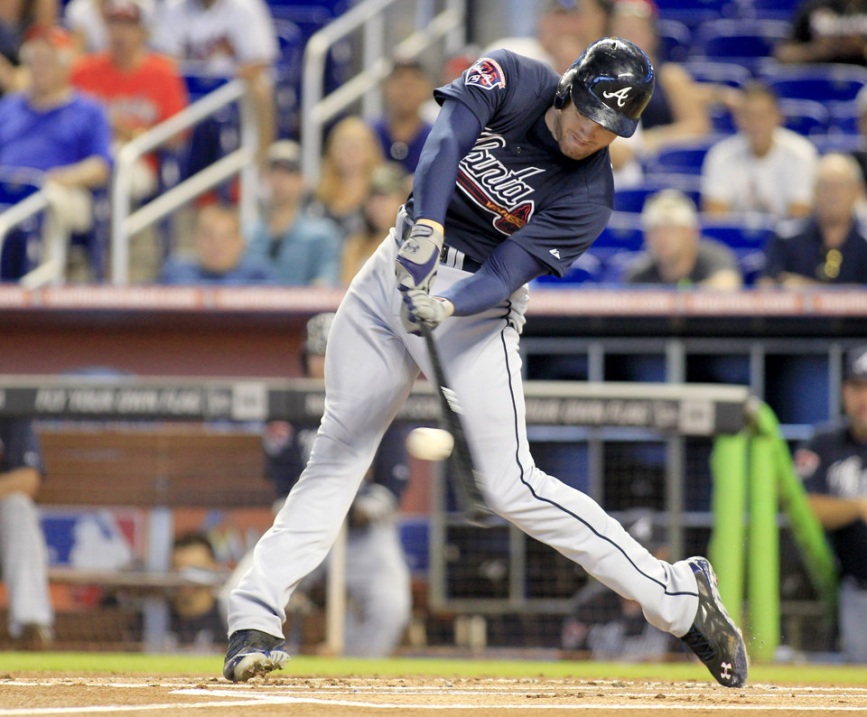 Photo - Atlanta Braves' Freddie Freeman flies out to center field in the first inning of play against the Miami Marlins during a baseball game in Miami, Sunday, June 1, 2014. (AP Photo/Joe Skipper)