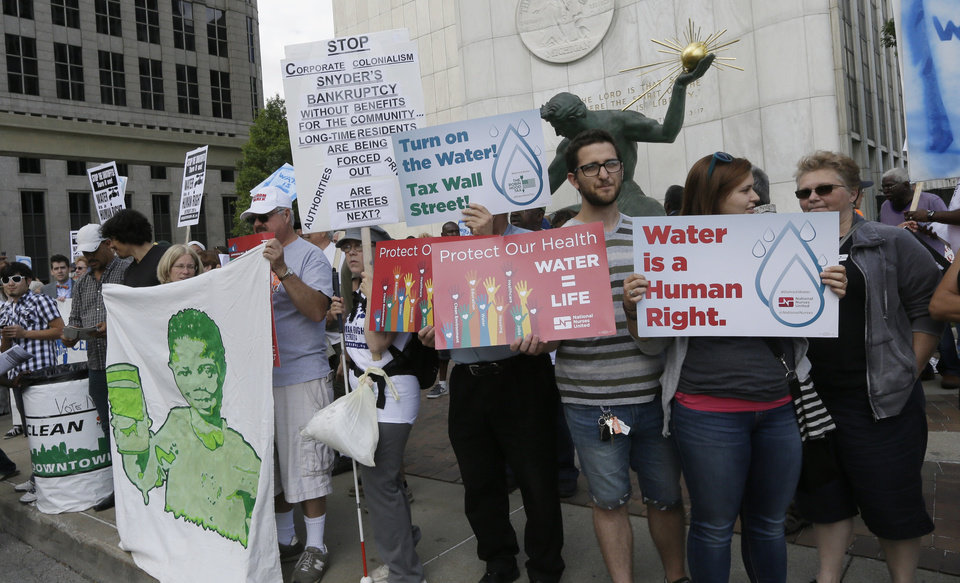 Photo - People stand outside Detroit City Hall, protesting thousands of residential water-service shutoffs by Detroit's water department, during a rally in Detroit, Thursday, July 24, 2014. (AP Photo)